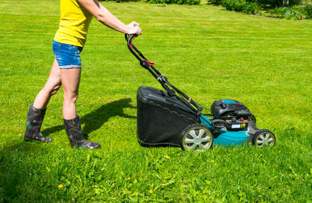 grass cutting: Beautiful girl cuts the lawn, Mowing lawns, Lawn mower on green grass, mower grass equipment, mowing gardener care work tool, close up view, sunny day
