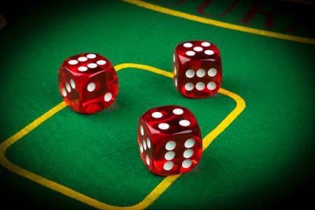 gambler: risk concept - playing dice on a green gaming table