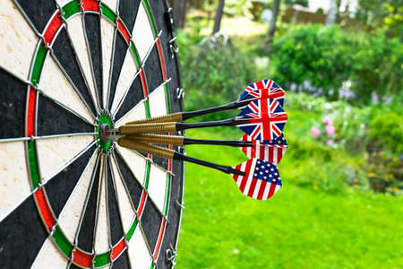 Metal darts have hit the red bullseye on a dart board. Darts Game. Darts arrow in the target center darts in bulls eye close up. Success hitting