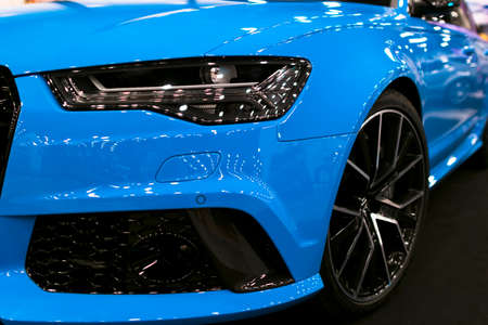 Front view of blue modern luxury sport car. Car exterior details. Headlight of a modern sport car. The front lights of the car