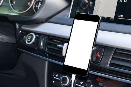 Smartphone in a car use for Navigate or GPS. Driving a car with Smartphone in holder. Mobile phone with isolatede white screen. Blank empty screen. copy space. Empty space for text. modern car interior details.