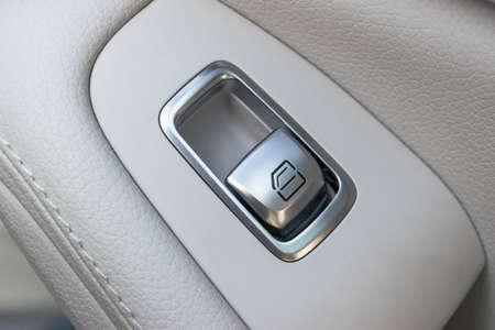 door handle: Car white leather interior details of door handle with windows controls and adjustments. Car window controls of modern car.