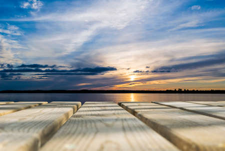 counter top: Wooden board empty table in front of sunset sea & sky background. Perspective wood floor over sea and sunset sky & summer concepts. Stock Photo