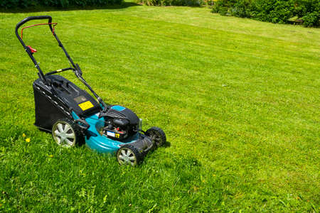 Mowing lawns Lawn mower on green grass mower grass equipment mowing gardener care work tool close up view sunny day Stock Photo