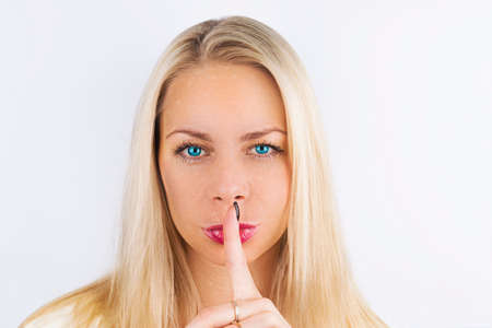 Shh! Womens secrets. Beautiful blond Woman with blue eyes holding her finger to her pink lips in a gesture for silence. Making silence sign with finger near lips.