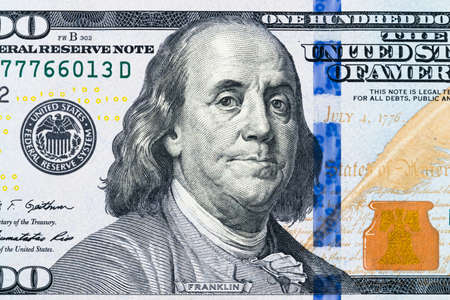 Close up overhead view of Benjamin Franklin face on 100 US dollar bill. US one hundred dollar bill closeup. Heap of one hundred dollar bills on money background. Stock fotó