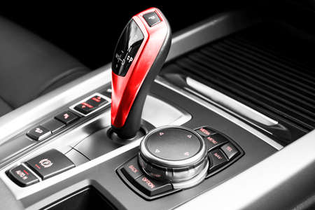 Red Automatic gear stick of a modern car, car interior details. Black and white