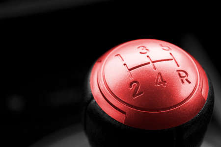 Close up view of a red gear lever, manual gearbox, car interior details