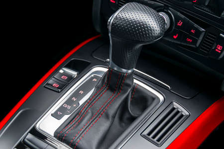 Automatic gear stick with red stich of a modern car. Car interior details. Dashboard with buttons Фото со стока