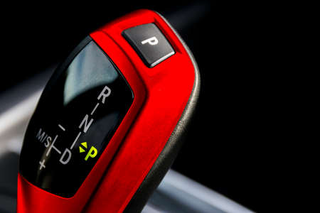 Red Automatic gear stick of a modern car, car interior details, close up view