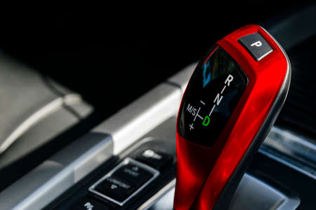 Red Automatic gear stick of a modern car. Car interior details