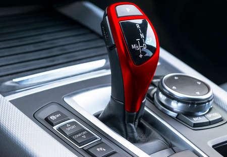 Red Automatic gear stick of a modern car, car interior details, close up