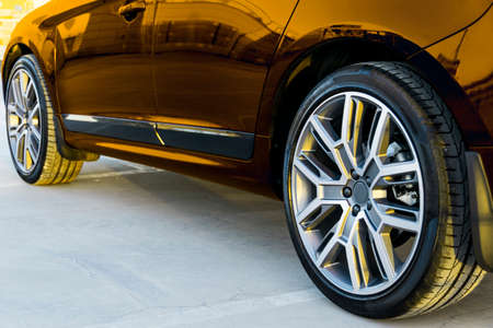 Side view of a car. Tire and alloy wheel of a modern gold car on the ground at the sunset. Car exterior details Stock Photo
