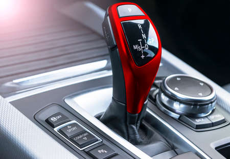 Red Automatic gear stick of a modern car, car interior details, close up. Soft lighting. Abstract view