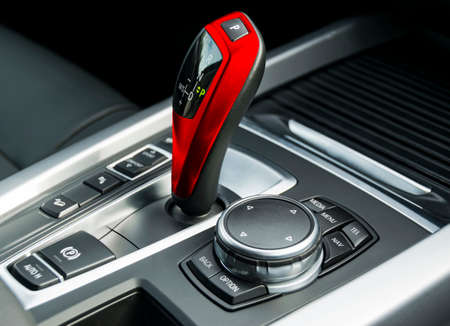 Automatic gear stick (transmission)  of a modern car, multimedia and navigation control buttons. Car interior details