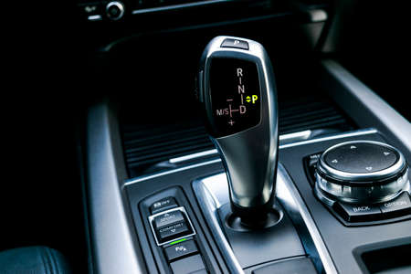 Automatic gear stick (transmission) of a modern car, multimedia and navigation control buttons. Car interior details. Transmission shift.