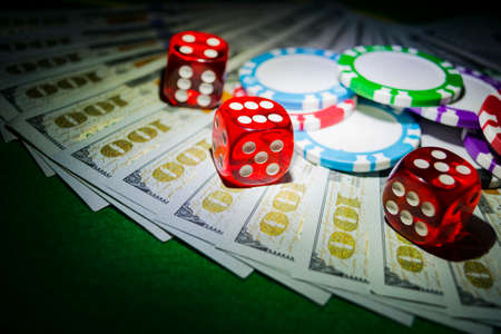 Stack of Poker chips with dice rolls on a dollar bills, Money. Poker table at the casino. Poker game concept. Playing a game with dice. Casino dice rolls. Concept for business risk. chance good luck