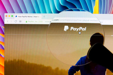 Sankt-Petersburg, Russia, December 5, 2017: Paypal homepage on a Apple imac monitor screen under magnifying glass. PayPal is an international e-commerce business allowing payments and money transfers.