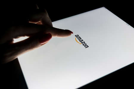 Sankt-Petersburg, Russia, January, 9 2017:  A womans hand is touching screen on Apple iPad Pro at night Amazon.com homepage application. Amazon is the largest online seller platform Editorial