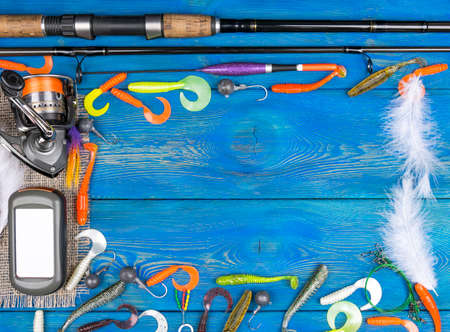 Fishing tackle - fishing spinning, fishing line, hooks, navigator and reel on blue wooden background