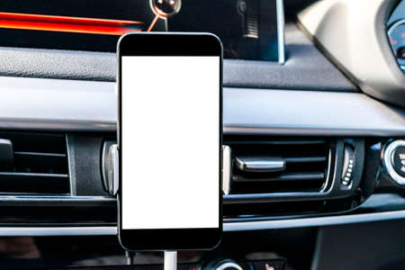 Smartphone in a car use for Navigate or GPS. Driving a car with Smartphone in holder. Mobile phone with isolatede white screen. Blank empty screen. copy space. Empty space for text. modern car interior details. Imagens - 95352655