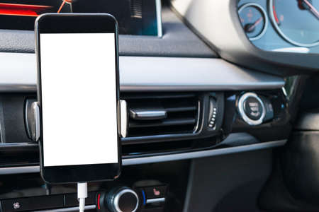 Smartphone in a car use for Navigate or GPS. Driving a car with Smartphone in holder. Mobile phone with isolated white screen. Blank empty screen. copy space. Empty space for text. modern car interior details.