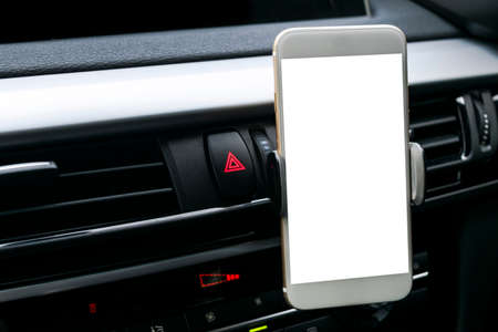 Smartphone in a car use for Navigate or GPS. Driving a car with Smartphone in holder. Mobile phone with isolatede white screen. Blank empty screen. copy space. Empty space for text. car interior
