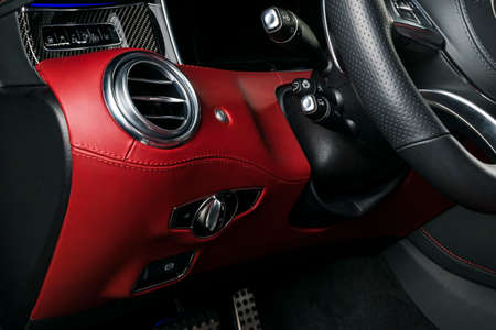 AC Ventilation Deck in Luxury modern Car Interior. Modern car interior details with red and black leatherwith red stitchin. Carbon panel. Perforated leather steering wheel