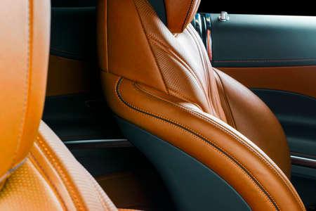 Modern Luxury car inside. Interior of prestige modern car. Comfortable leather red seats. Orange perforated leather. Modern car interior details