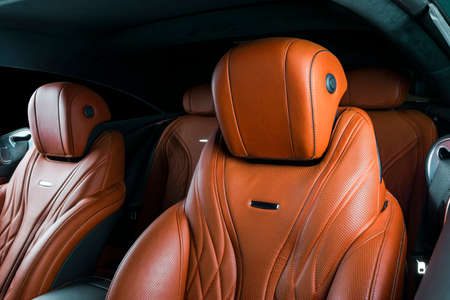 Modern Luxury car inside. Interior of prestige modern car. Comfortable leather red seats. Orange perforated leather cockpit with isolated Black background. Modern car interior details