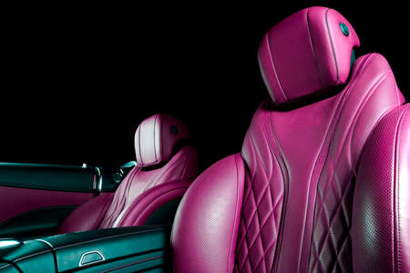 Modern Luxury car inside. Interior of prestige modern car. Comfortable leather seats. Pink perforarated leather cockpit with isolated Black background. Modern car interior Stock Photo