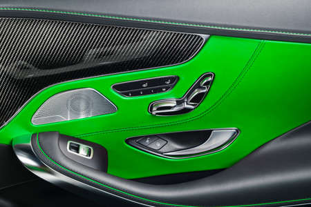Car green leather and carbon interior details of door handle with windows power seat controls and adjustments. Luxury car inside. Modern car interior details