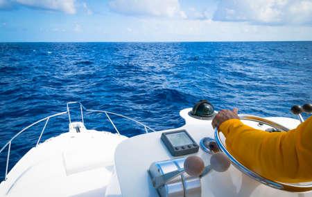 Main du capitaine sur le volant du bateau à moteur dans l'océan bleu en raison de la journée de la pêche