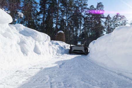 Snowblower at work on a winter day. Snowplow removing snow after blizzard. Clearing the ice. Snow removal machine. Clear driveway with a snowblower. Snow blower. Snow plower.