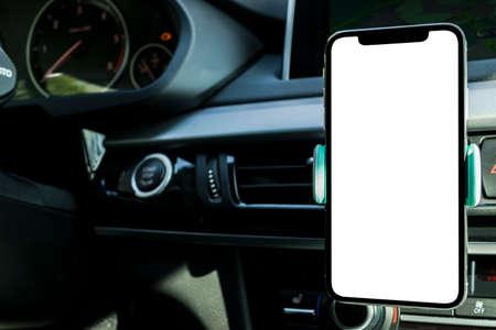 Uso de teléfono inteligente en un automóvil para Navigate o GPS. Conducir un automóvil con Smartphone en el soporte. Teléfono móvil con pantalla en blanco aislado. Pantalla vacía en blanco. copia espacio Espacio vacío para texto. interior del coche moderno