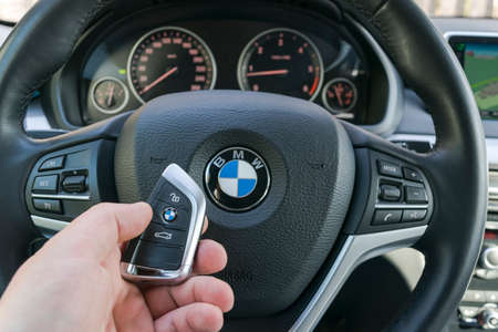 Sankt-Petersburg Russia, April 4, 2018: Man's hand holding a wireless BMW X5 F15 car key in black leather car interior. Modern Car interior details. Car detailing. Car inside.