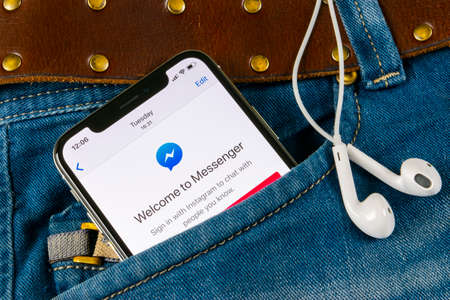 Sankt-Petersburg, Russia, April 14, 2018: Facebook messenger application icon on Apple iPhone X screen close-up in jeans pocket. Facebook messenger app icon. Online internet social media network. Social media app