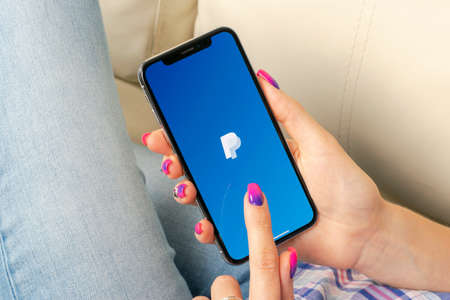 Sankt-Petersburg, Russia, May 30, 2018: PayPal application icon on Apple iPhone X smartphone screen in woman hands. PayPal app icon. PayPal is an online electronic finance payment system.