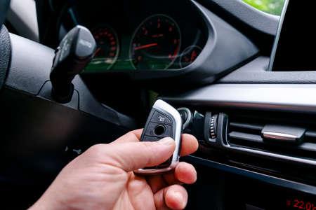 Closeup inside vehicle of man hand holding wireless key ignition. Start engine key. Hand holding car key remote. Modern car background. Interior details. Car detailing