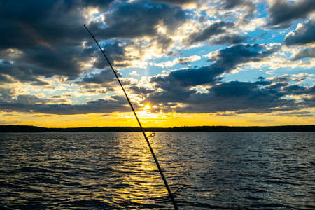 Fishing road silhouette during sunset. Fishing pole against ocean at sunset. Fishing rod in a saltwater boat during fishery day in the ocean.