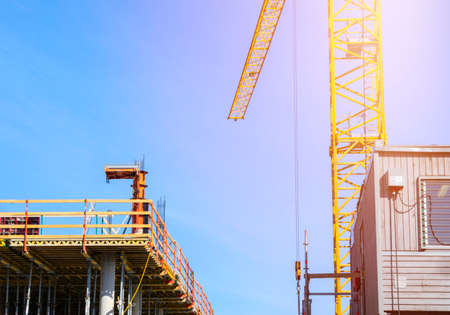 Construction crane tower on blue sky background. Crane and building working progress. Worker. Empty Space for text. Construction concept. Site. New buildings with a crane. Tower crane