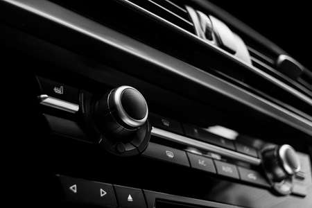 Air conditioning button inside a car. Climate control AC unit in the new car. Modern car interior details. Car detailing. Black perforated leather interior. Black and white