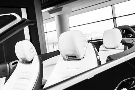 Modern Luxury car inside. Interior of prestige modern cabriolet car. Comfortable leather seats. White perforated leather. Modern car interior details. Cabrio. Black and white
