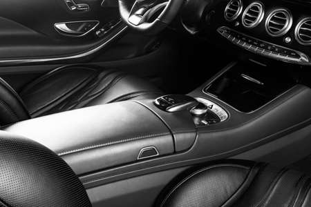 Modern Luxury car inside. Interior of prestige modern car. Comfortable leather seats. Perforated leather cockpit. Steering wheel and dashboard. automatic gear stick shift. Car interior. Black and white Foto de archivo