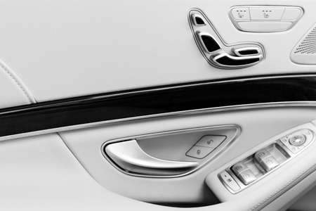 Door handle with Power seat contol buttons of a luxury passenger car. White leather interior of the luxury modern car. Modern car interior details. Car detailing. Black and white