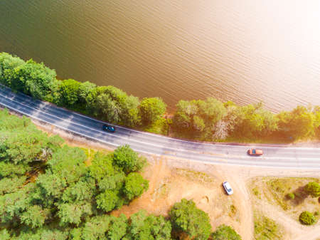 Aerial view of highway with car. Aerial view of a country road with moving car. Car passing by. Aerial road. Aerial view flying. Captured from above with a drone. Soft lighting Stockfoto