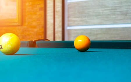 Billiard table close up. Playing billiard. Billiards balls and cue on green billiards table. Billiard sport concept. Pool billiard game.