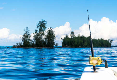 Fishing rod in a saltwater private motor boat during fishery day in blue ocean. Successful fishing concept Stock Photo