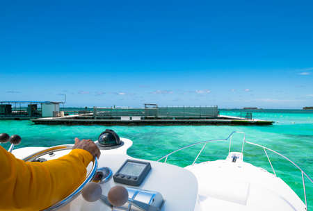 Hand of captain on steering wheel of motor boat in the blue ocean during the fishery day. Success fishing concept. Ocean yacht Editorial