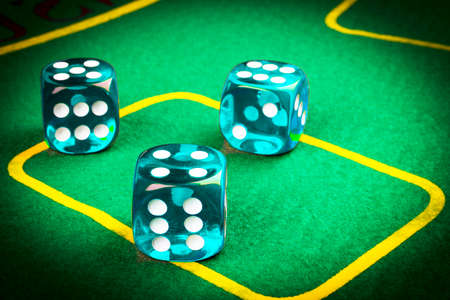 risk concept - playing dice on a green gaming table. Playing a game with dice. Blue casino dice rolls. Rolling the dice concept for business risk, chance, good luck or gambling